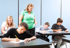 Supervised Testing in School. Teacher supervising high school students as they take and achievement test royalty free stock photography