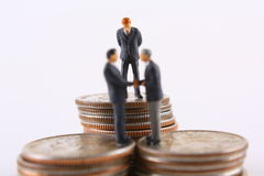 Supervising Concept. Miniature businessman watching two other businessmen shake hands Royalty Free Stock Photos
