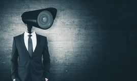 Supervision and guard concept. CCTV camera headed businessman standing on dark concrete background with copy space. Supervision and guard concept royalty free stock photo