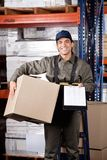 Supervisor With Clipboard And Cardboard Box. Portrait of young male supervisor holding clipboard and cardboard box at warehouse Stock Images