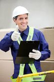 Supervisor With Clipboard Gesturing Thumbs Up. Portrait of supervisor with clipboard gesturing thumbs up at warehouse Royalty Free Stock Images