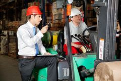 Supervisor With Clipboard Instructing Forklift Royalty Free Stock Images