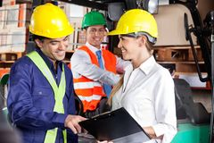 Supervisor Communicating With Foreman At Warehouse. Young female supervisor communicating with foreman at warehouse Royalty Free Stock Photo