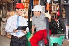 Supervisor Communicating With Forklift Driver. At warehouse Stock Photo