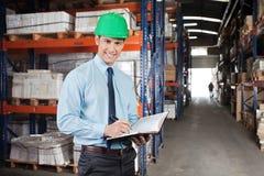 Supervisor confiado con el libro en Warehouse Foto de archivo