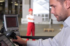 Supervisor at control panel in factory. Other worker with box in background stock photo