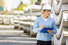 Supervisor de sexo masculino con el tablero que examina la acción en el sitio Imagen de archivo