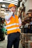 Supervisor die Celtelefoon met behulp van bij Pakhuis Stock Afbeelding