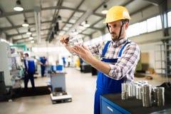 Supervisor die kwaliteitscontrole en pruductioncontrole in fabriek doen stock afbeelding