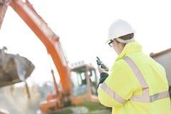 Supervisor die walkie-talkie met behulp van bij bouwwerf tegen duidelijke hemel Stock Afbeeldingen