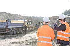 Supervisor explaining plan to colleague at construction site Royalty Free Stock Photo
