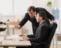 Supervisor explaining work to young businessman. Supervisor gesturing and explaining work to young businessman at desk Royalty Free Stock Images