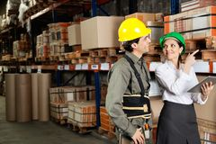 Supervisor With Foreman Pointing At Stock On. Female supervisor with foreman pointing at stock on shelves in warehouse stock photo