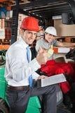 Supervisor And Forklift Driver Gesturing Thumbs Up. Portrait of supervisor and forklift driver gesturing thumbs up at warehouse Stock Image