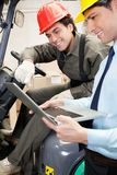 Supervisor And Forklift Driver Using Laptop. Young male supervisor and forklift driver using laptop at warehouse Stock Photos