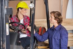 Supervisor In Forklift Shaking Hands With Stock Image