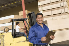 Supervisor And Forklift Truck Driver. Portrait of a male supervisor with clipboard and forklift truck driver in the background Stock Images
