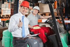 Supervisor Gesturing Thumbs Up At Warehouse. Portrait of supervisor gesturing thumbs up with forklift driver sitting behind Stock Photography
