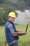 Supervisor with helmet and laptop computer Royalty Free Stock Photo