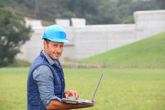 Supervisor with helmet and laptop computer Royalty Free Stock Photography