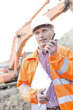 Supervisor holding clipboard while using walkie-talkie at construction site Royalty Free Stock Image