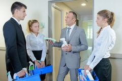 Supervisor with hotel personnel looking at cleaning products. Cleaning royalty free stock images