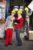 Supervisor Instructing Foreman At Warehouse. Young female supervisor instructing foreman at warehouse Royalty Free Stock Photo