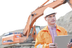 Supervisor looking away while holding clipboard at construction site Royalty Free Stock Photography