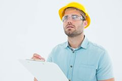 Supervisor looking away while writing on clipboard. Male supervisor looking away while writing on clipboard on white background Stock Image