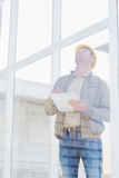 Supervisor looking up while writing on clipboard. Male supervisor looking up while writing on clipboard in office Royalty Free Stock Photography