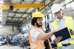 Supervisor with manual worker discussing over clipboard in metal industry royalty free stock photo