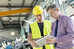 Supervisor and manual worker using digital tablet in metal industry stock image