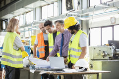 Supervisor and manual workers discussing over blueprints in industry stock photo