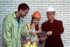 Supervisor mostrado os dados da tabuleta à equipe da manutenção fotografia de stock royalty free
