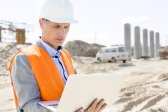 Supervisor que usa el ordenador portátil en el emplazamiento de la obra el día soleado Fotografía de archivo libre de regalías