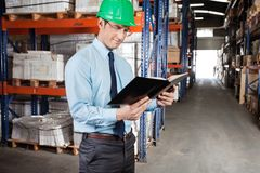 Supervisor Reading Book At Warehouse Royalty Free Stock Photo