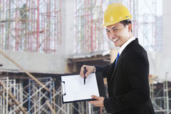 Supervisor showing blank clipboard. Smiling supervisor showing blank clipboard shot at workplace outdoor Stock Photography