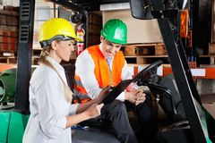 Supervisor Showing Clipboard To Colleague Sitting. Female supervisor showing clipboard to colleague sitting in forklift at warehouse Stock Image