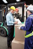 Supervisor Showing Clipboard To Foreman. Happy supervisor showing clipboard to young foreman at warehouse Royalty Free Stock Photo