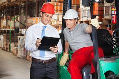 Supervisor Showing Clipboard To Foreman. Young supervisor showing clipboard to foreman at warehouse Royalty Free Stock Photography