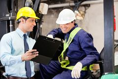 Supervisor Showing Clipboard To Forklift Driver. At warehouse Royalty Free Stock Image