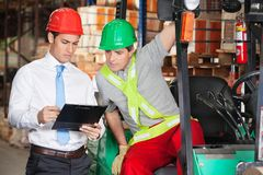 Supervisor Showing Clipboard To Forklift Driver. Young male supervisor showing clipboard to forklift driver at warehouse Stock Image