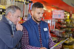Supervisor showing clipboard to worker. Warehouse Royalty Free Stock Photography
