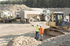 Supervisor showing something to colleague at construction site Royalty Free Stock Photo