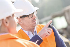 Supervisor showing something to colleague at construction site Royalty Free Stock Photos