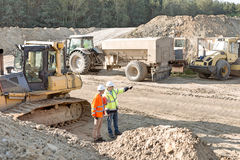 Supervisor showing something to colleague at construction site Royalty Free Stock Photography