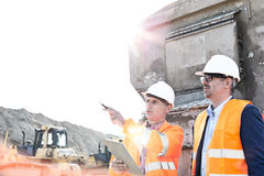 Supervisor showing something to colleague at construction site on sunny day Royalty Free Stock Photos