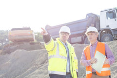 Supervisor showing something to colleague while discussing at construction site Royalty Free Stock Image