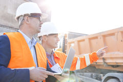 Supervisor showing something to colleague holding laptop at construction site Royalty Free Stock Photo
