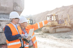 Supervisor showing something to coworker holding laptop at construction site royalty free stock image